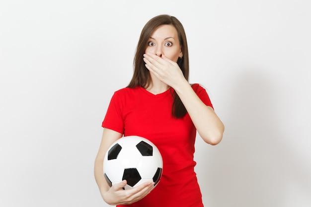 Schöne europäische junge frau, fußballfan oder spieler in roter uniform bedecken den mund mit der hand, halten fußball isoliert auf weißem hintergrund. sport, fußball spielen, gesundheit, gesundes lebensstilkonzept.