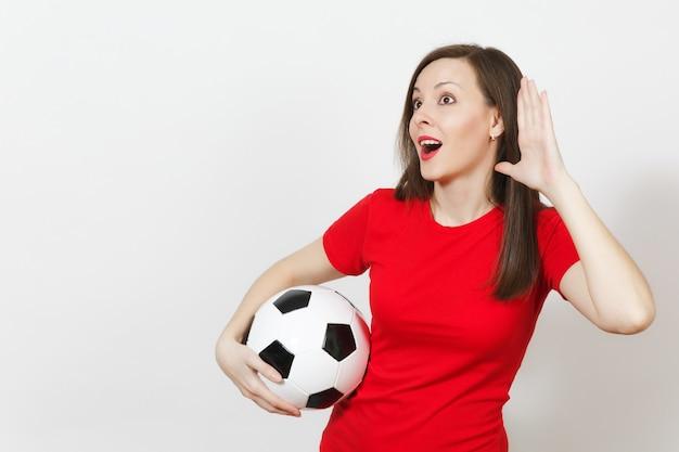 Schöne europäische junge frau, fußballfan oder spieler in roter uniform lauschen, hörende geste, halten fußball isoliert auf weißem hintergrund. sport spielen fußball, gesundheit, gesundes lifestyle-konzept.