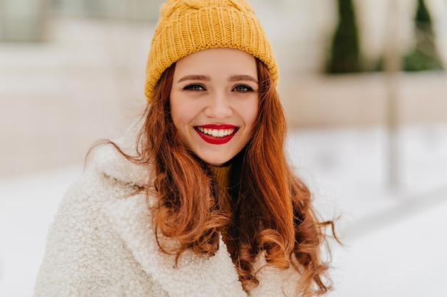 Schöne europäische junge frau in der strickmütze, die im winter lacht. foto des sinnlichen hübschen mädchens im stilvollen mantel.
