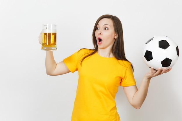 Schöne europäische junge fröhliche frau, fußballfan oder spieler in gelber uniform, die einen pintkrug bier hält, fußball isoliert auf weißem hintergrund. sport, fußball spielen, gesundes lifestyle-konzept.