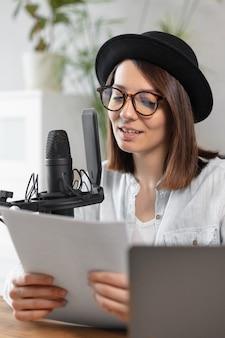 Schöne europäische podcasterin mit kopfhörern und mikrofon zeichnet podcast in aufnahme auf