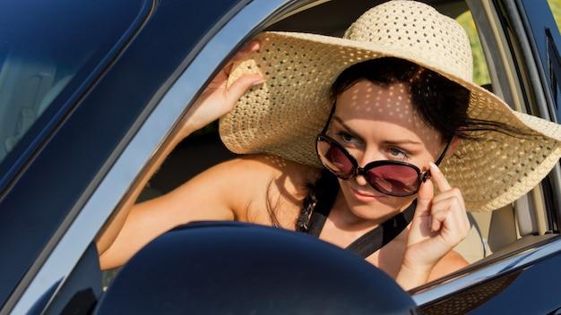 Schöne fahrerin in einem strohsonnenhut und einer sonnenbrille, die über ihre brille späht, die ihren seitenspiegel prüft