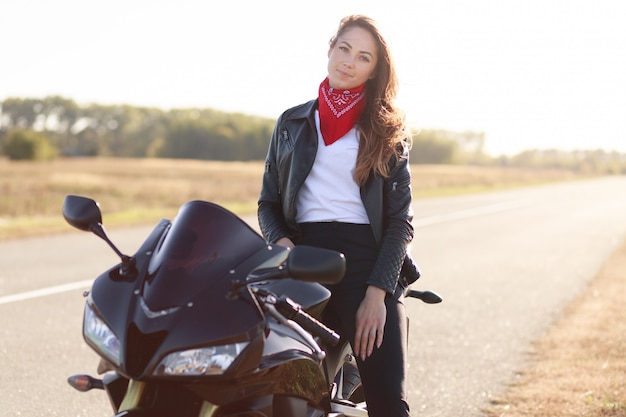 Schöne fahrerin sitzt auf schwarzem schnellem motorrad, gekleidete lederjacke, fährt mit dem motorrad durch das land, bleibt auf der seite stehen
