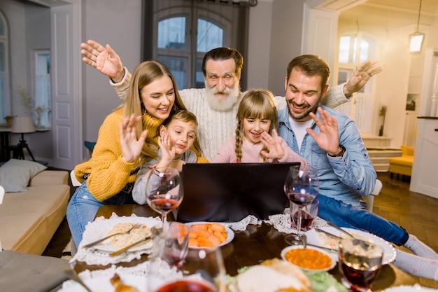 Schöne familie, am tisch mit abendessen sitzend, lächelnd, glücklich und mit laptop.