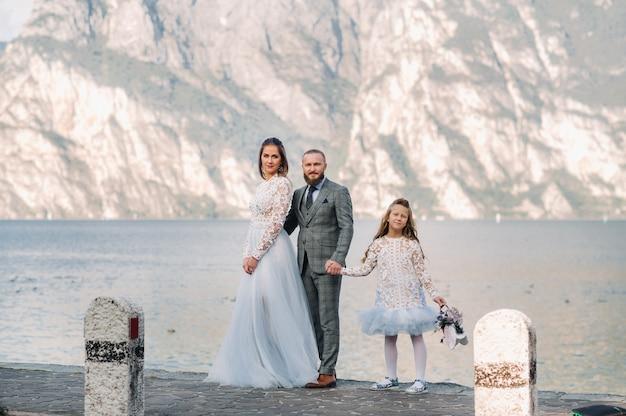 Schöne familie am ufer des gardasees in italien am fuße der alpen