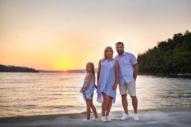 Schöne familie auf dem pier am meer während des sonnenuntergangs