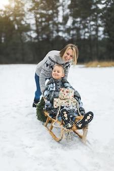 Schöne familie der jungen mutter und des sohnes, die verschneiten wintertag im freien genießen, der spaß schlittenfahren hat