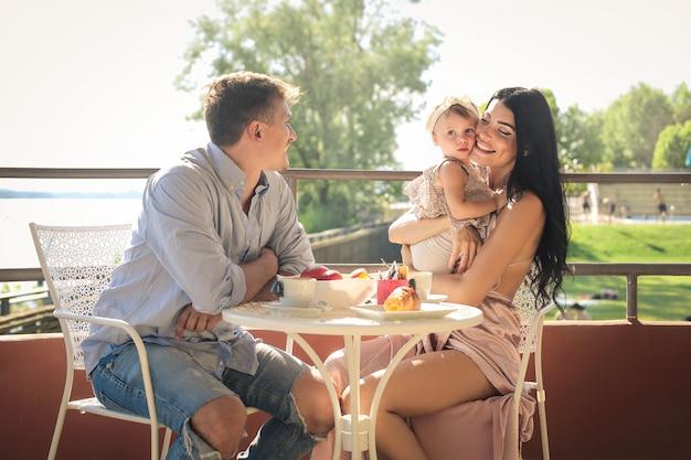 Schöne familie, die auf einer terrasse frühstückt