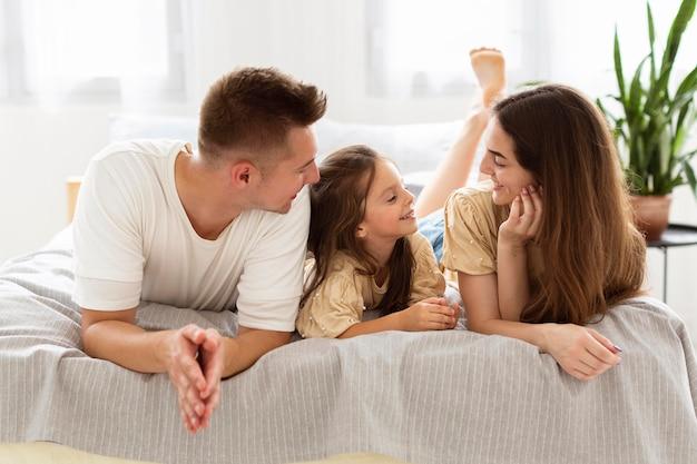 Schöne familie, die einen niedlichen moment zusammen im bett hat