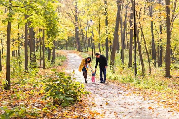 Schöne familie, die im herbstwald spazieren geht