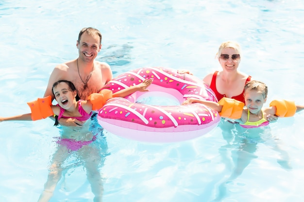 Schöne familie, die spaß in einem swimmingpool hat.