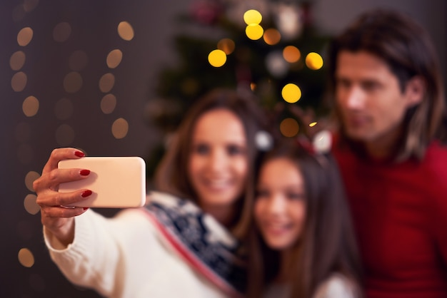 Schöne familie, die weihnachten zu hause feiert und selfie macht