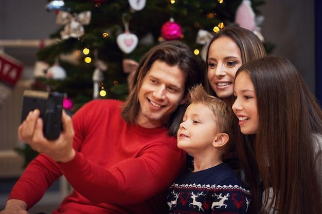 Schöne familie, die weihnachten zu hause feiert und sofortbilder macht