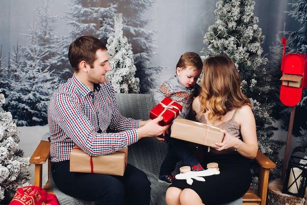 Schöne familie, die zusammen auf bank sitzt und weihnachtsgeschenke vor feiertagen genießt