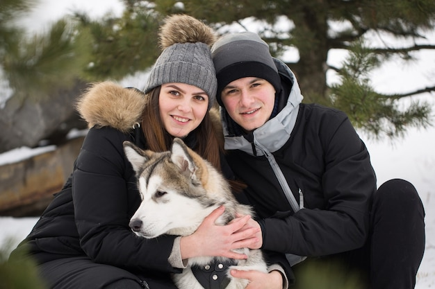 Schöne familie, ein mann und ein mädchen im winterwald mit hund. spielen sie mit dem hund siberian husky.