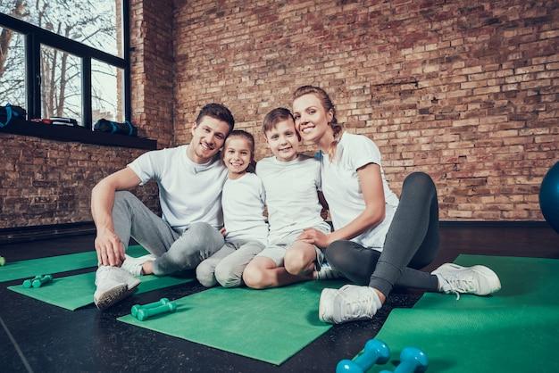 Schöne familie in den weißen t-shirts, die in der großen turnhalle sitzen.