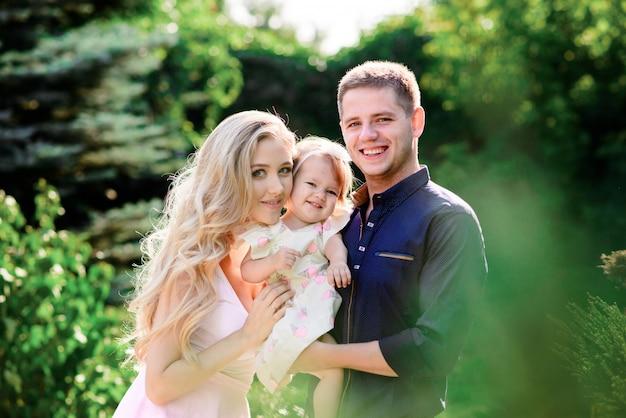 Schöne familie mit einer kleinen tochter in der natur.