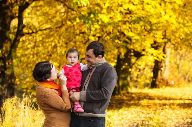 Schöne familie mit kleinem mädchen, das im herbstpark spaziert