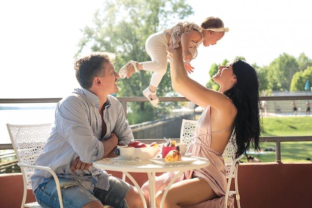 Schöne familie sitzt auf einer terrasse und frühstückt