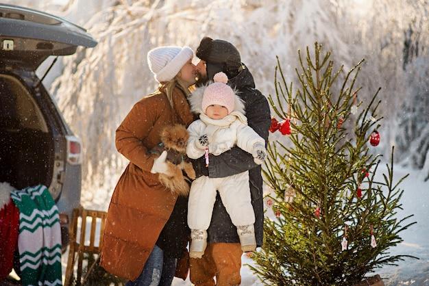 Schöne familie steht neben dem kofferraum eines suv im winterwald und feiert weihnachten
