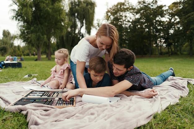 Schöne familie verbringt zeit miteinander und zeichnet in der natur