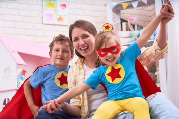 Schöne familienmutter und -tochter mit dem sohn kleideten in den kostümen von superhelden an