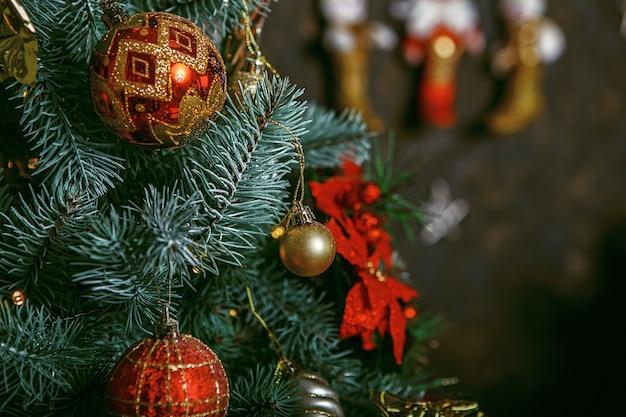 Schöne farbe weihnachtsdekorationen hängen am weihnachtsbaum mit glänzendem glanz