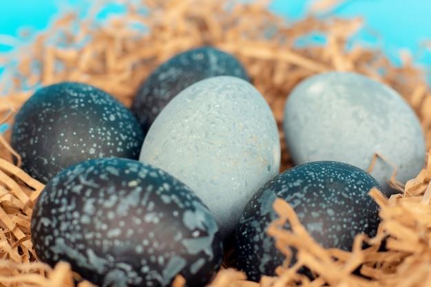 Schöne farbige ostereier von dunkler farbe, wie ein kosmos, liegen in einem nest