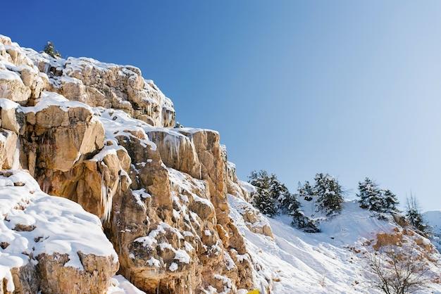 Schöne felsenberge, die im winter bei sonnigem wetter in usbekistan in der nähe des ferienortes beldersay mit schnee bedeckt sind. tian shan gebirgssystem