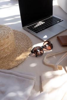 Schöne feminine mode-sommer-accessoires. stilvolle damensonnenbrille, strohhut, einkaufstasche, laptop in verschwommenen sonnenlichtschatten shadow