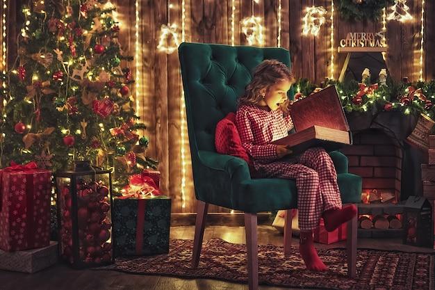 Schöne ferien. nettes kleines kinderöffnungsgeschenk nahe weihnachtsbaum. das mädchen lacht und genießt das geschenk.