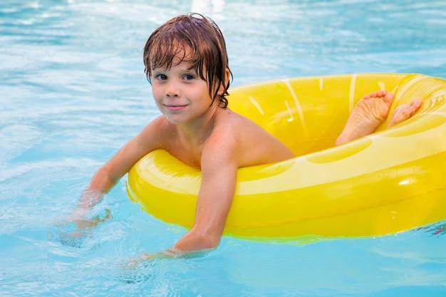Schöne ferienzeit. junge, der spaß im pool mit schwimmer hat. gesicht emotionen. sommergefühl.