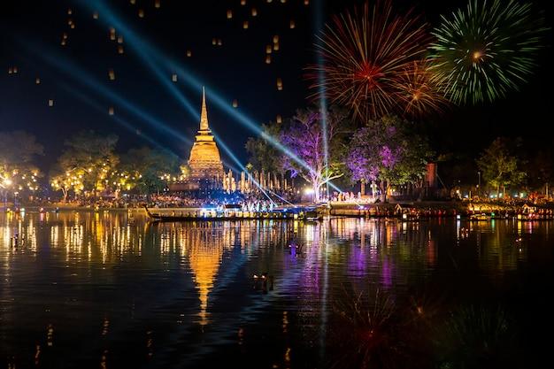 Schöne feuerwerksreflexion über altem pagoden-loy-krathong-festival