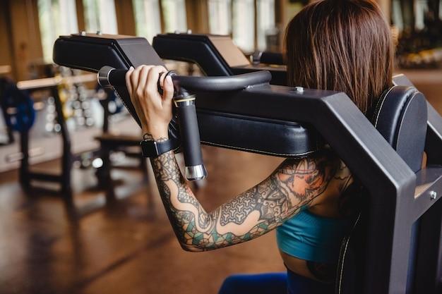 Schöne fitnes mädchen ist im fitnessstudio beschäftigt übung macht die brust stärkt