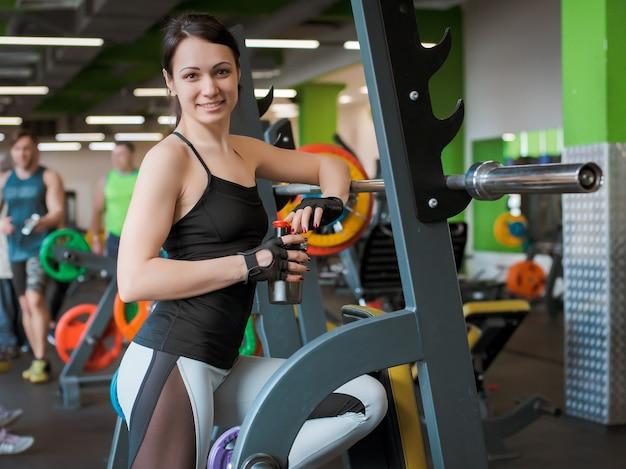 Schöne fitness-frau, die langhantel anhebt. sportliche frau, die gewichte anhebt. passendes mädchen, das muskelaufbau trainiert. fitness-bodybuilding