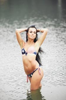 Schöne fitness junge frau im badeanzug mit amerikanischer flagge am strand