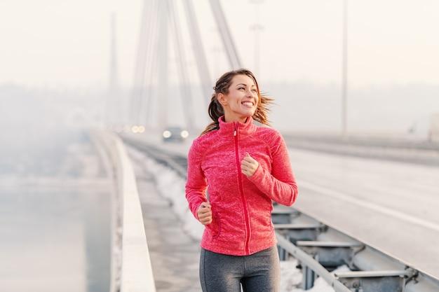 Schöne fitnessfrau, die am wintermorgen genießt. winter fitne