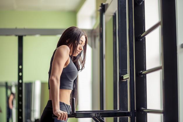 Schöne fitnessfrau, die übung auf parallelstangen innen tut. sportliches mädchen, das liegestütze auf stangen tut