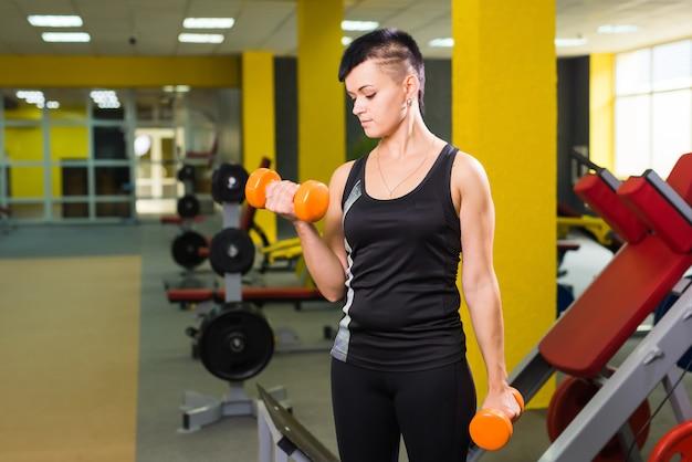 Schöne fitnessfrau mit anhebenden hanteln