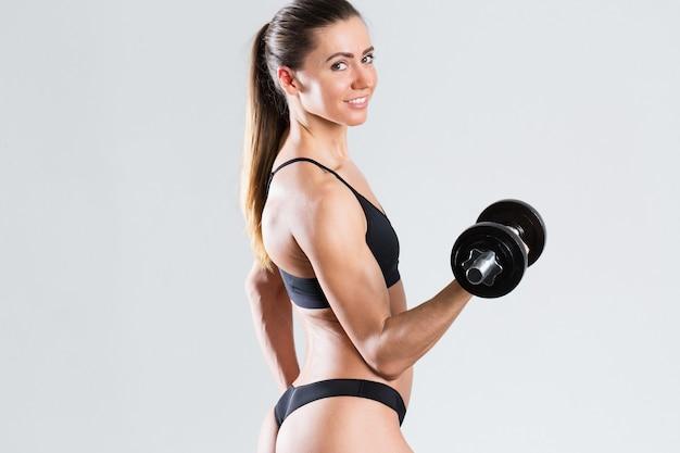Schöne fitnessfrau mit hanteln isoliert. bewegung und gesunder lebensstil.