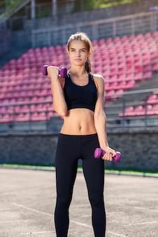 Schöne fitnessfrau mit perfektem körper, der workouts mit ultravioletten hanteln am stadion tut