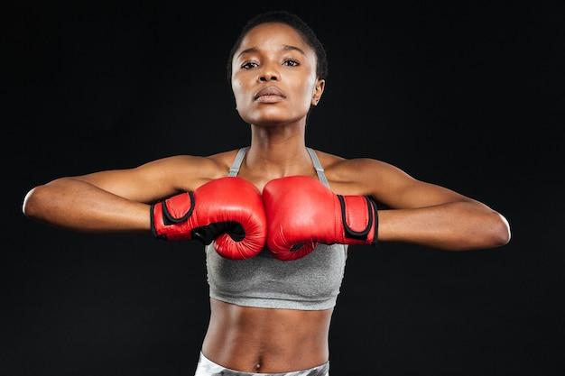 Schöne fitnessfrau posiert mit boxhandschuhen auf schwarzer wand