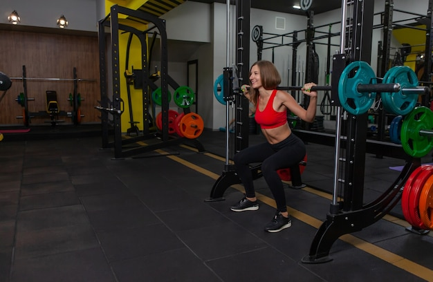 Schöne, fitte frau, die kniebeugen im trainingsgerät im fitnessstudio übt