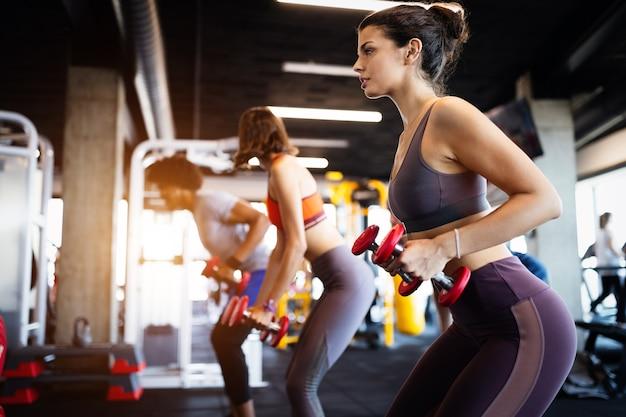 Schöne, fitte, glückliche frauen, die im fitnessstudio trainieren