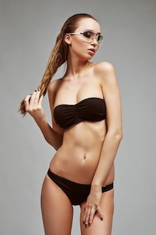 Schöne, fitte und sportliche frau im badeanzug. konzept für fettabbau, fettabsaugung und entfernung von cellulite.