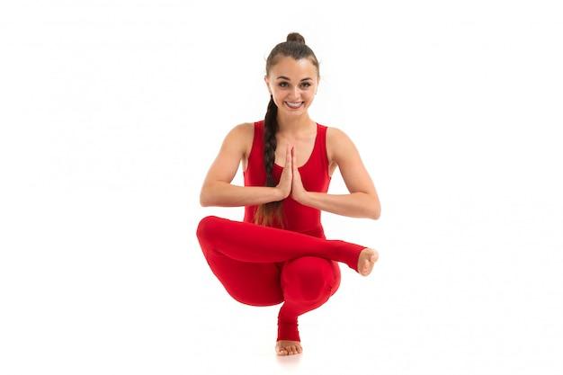 Schöne flexible frau, die yoga-posen auf weißem hintergrund tut
