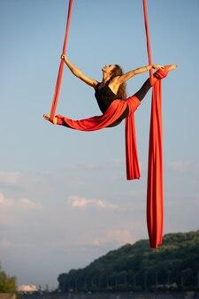 Schöne flexible künstlerin mit luftseide auf himmels- und flusshintergrund
