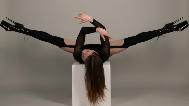 Schöne flexible mädchen pole tänzerin in high heels posiert im studio
