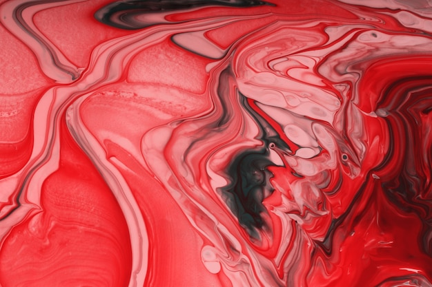 Schöne flüssige textur des nagellacks. einfarbiger roter hintergrund mit kopienraum. flüssige kunst, gießtechnik. gut als digitales dekor.