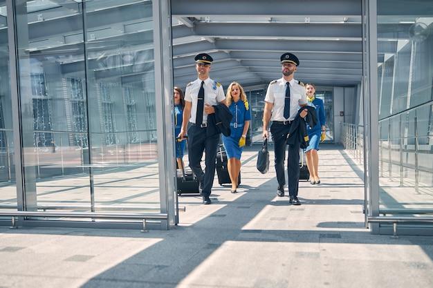 Schöne flugbegleiter und gutaussehende piloten, die trolleys tragen und zum ausgang des flughafenterminals gehen